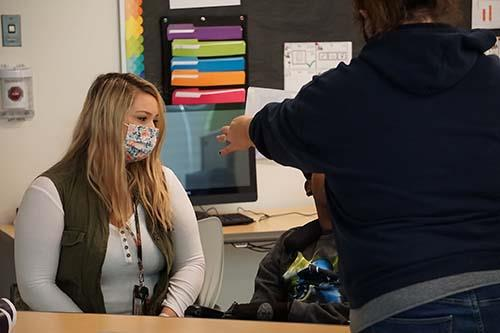 teacher working with students wearing mask