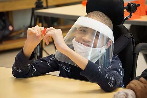 student wearing face shield and smiling