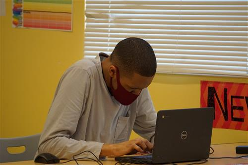 student wearing mask working on computer