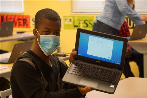 student wearing mask and holding laptop computer