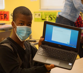 student holding laptop and wearing mask
