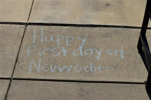 welcome message written in chalk on sidewalk