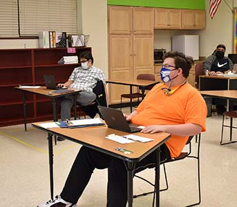student sitting in class wearing mask