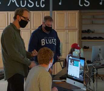 students and teacher working on computer wearing masks