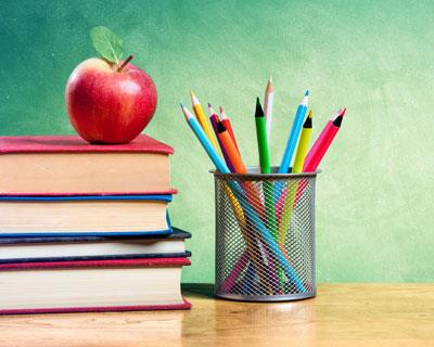apple with books and pencils on desk