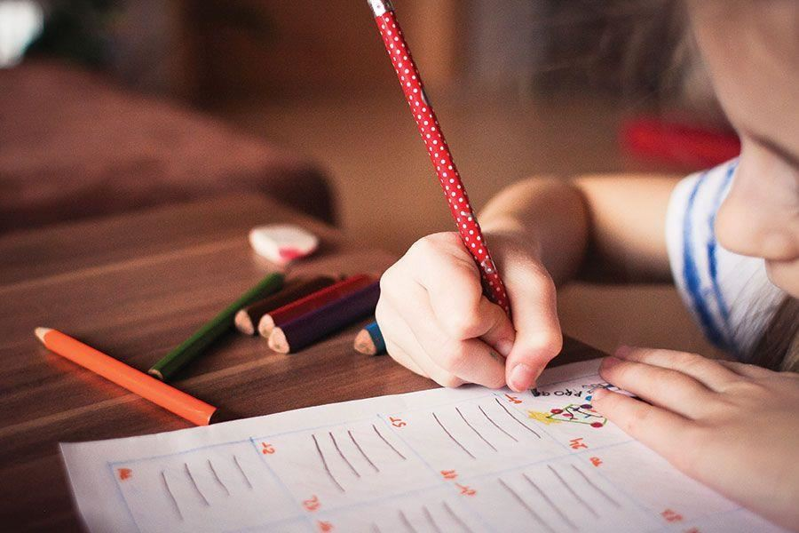 Child working on homework with color pencils