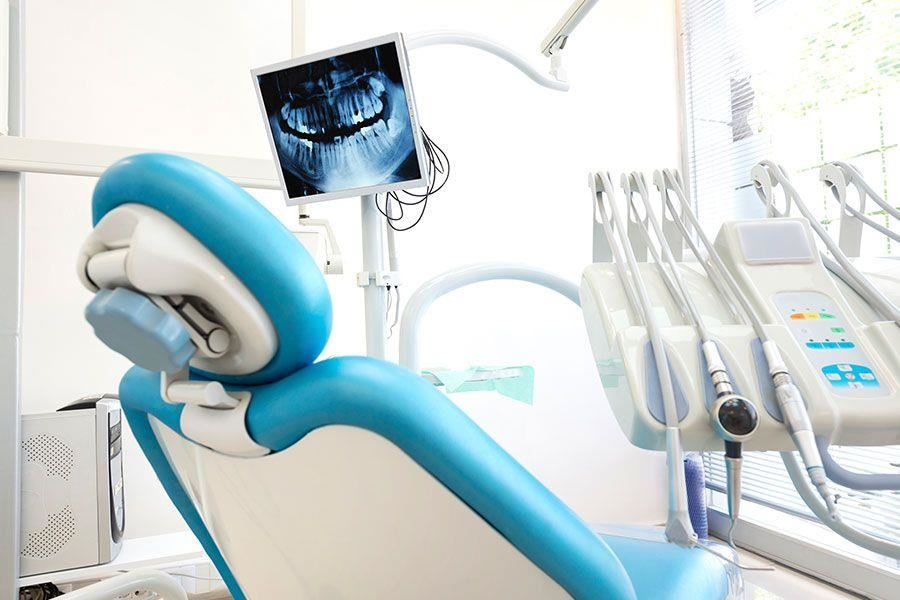 A dental chair with dental tools and an x-ray photograph