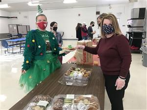 Litzsinger School principal, Kathy Russ, serves treats to a staff member
