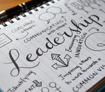leadership words written on notebook page