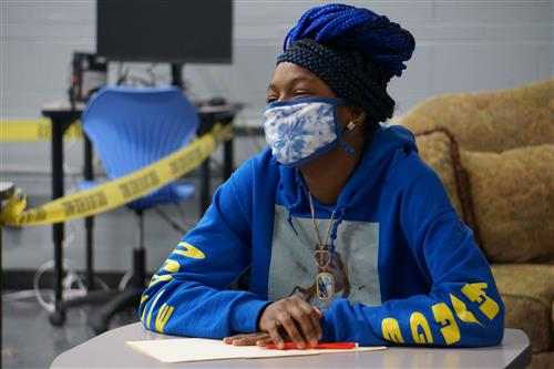 student sitting at desk wearing mask